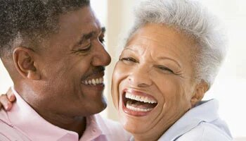 Elderly couple laughing and hugging
