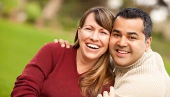 Middle-aged couple smiling and hugging outdoors