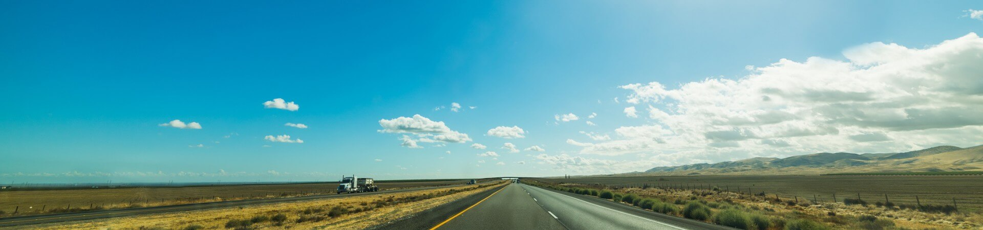 Open highway surrounded by fields with a bright blue sky above